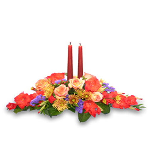 Centerpiece design contains orange roses, red gladiolus, rust & gold variegated cushion poms, purple statice, red hypericum, Italian ruscus and salal tips in a low profile container with 2 taper candles.<br/><br/>