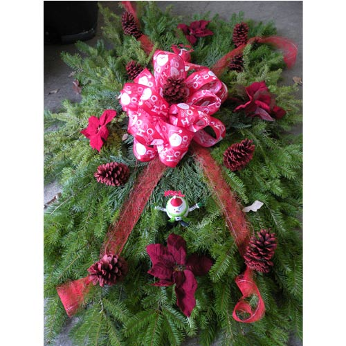 Remember your loved ones this holiday season with a hand-made grave blanket. This 6 x 3 foot grave blanket is made of mixed Christmas evergreens and decorated with red streamers, holiday ribbon, red pine cones, and red silk poinsettia leaves hand-delivered to your loved one's resting place.