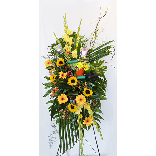 A Wylie Flower Shop exclusive tribute. This garden themed standing easel is an original design and can be further customized to your wishes. This design is a fitting memorial to remember loved ones and friends who enjoyed the peace and rewards from working in their gardens.<br/><br/>