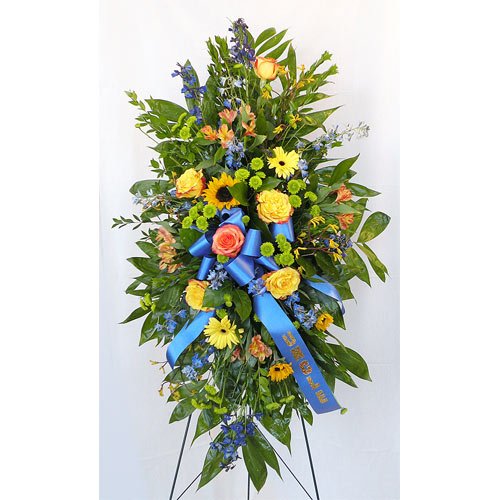 A Wylie Flower Shop exclusive tribute. A beautiful standing easel of bright colors with blue hues along with blue ribbons honoring the memory of a family member, loved one, or friend.<br/><br/>