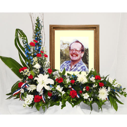 A Wylie Flower Shop tribute exclusive. This tribute arrangement themed in red, white, and blue, is a beautiful floral frame to memorialize a patriotic loved one while sharing remembrances with all.<br/><br/>