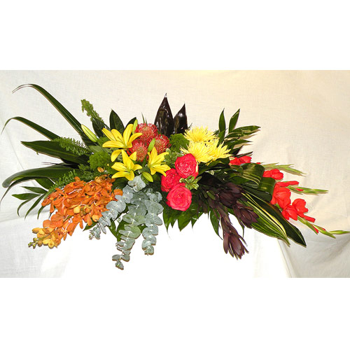 A Wylie Flower Shop tribute exclusive. When choosing flowers for a passing, we often reflect on the personality, traits, and hobbies of the person being honored. This tropical style tribute speaks volumes of their spirit and your memories.<br/><br/>