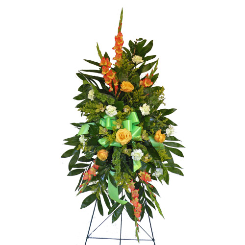 A Wylie Flower Shop exclusive design. A traditional standing easel containing variegated yellow/orange gladiolus, green carnations, cymbidium orchids, yellow roses, solidago, bells of ireland, with palm leaf greenery on a standing easel.<br/><br/>