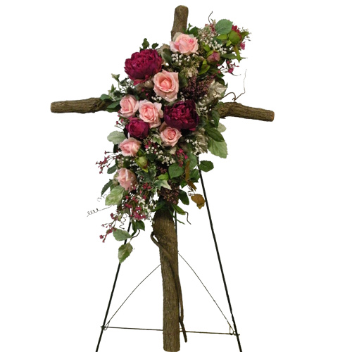 A Wylie Flower Shop exclusive tribute. A real wooden cross is decorated with silk flowers to make a long lasting tribute to a friend or loved one. In this design, a mixture of pink tone silks are accented by silk baby's breath, mixed silk greenery, and spanish moss, are placed across a wooden cross attached to a standing easel. <br/><br/>